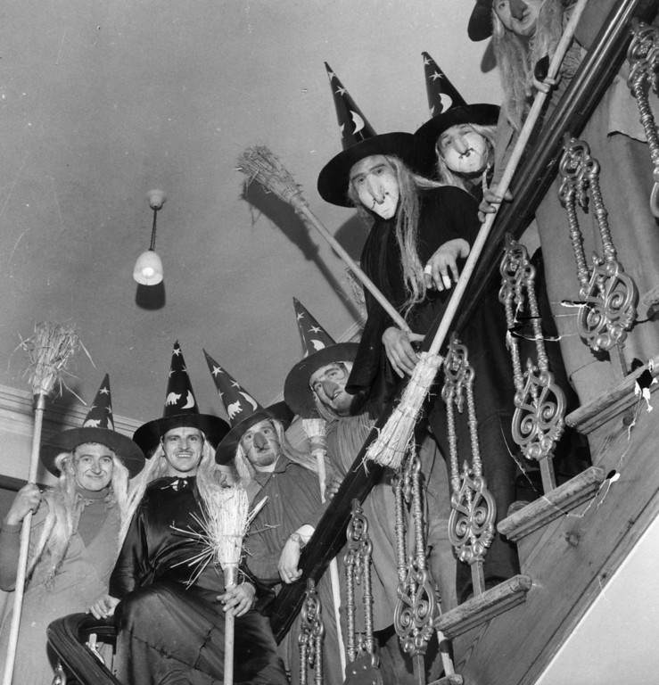 Description of . circa 1950:  A group of men in costume as witches, complete with brooms, to celebrate Halloween, line the staircase of a house.  (Photo by George Pickow/Three Lions/Getty Images)
