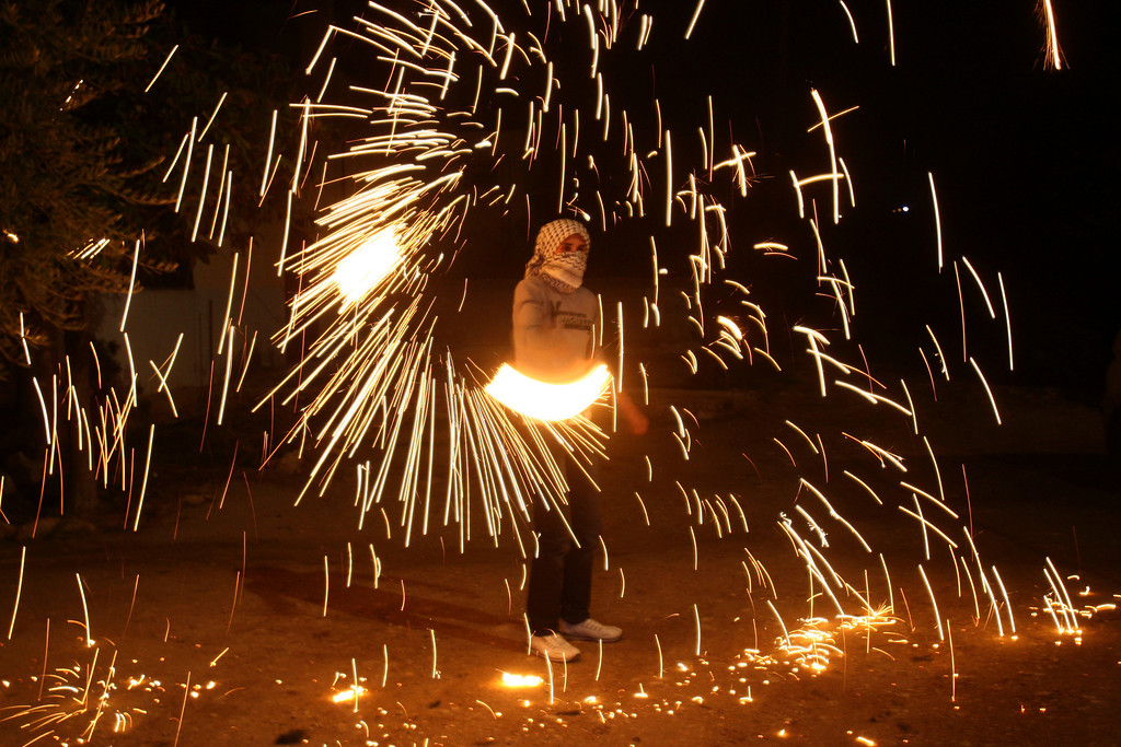Description of . A Palestinian youth plays with fireworks while Palestinian Authority President Mahmoud Abbas speaks to the United Nations General Assembly at the UN headquarters in New York, before the body votes on a resolution to upgrade the status of the Palestinian Authority to a nonmember observer state, in the West Bank city of Nablus, Thursday, Nov. 29, 2012. The Palestinians are certain to win U.N. recognition as a state on Thursday but success could exact a high price: delaying an independent state of Palestine because of Israel's vehement opposition.(AP Photo/Nasser Ishtayeh)