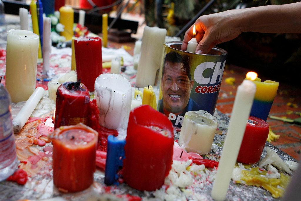 Description of . A woman lights candles during a ceremony for late President Hugo Chavez at the Bolivar square in Barinas, the capital of the state where he was born in western Venezuela, Friday, March 8, 2013.  (AP Photo/Esteban Felix)