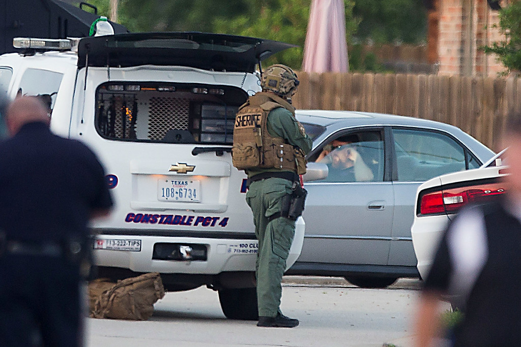 Description of . Law enforcement officers surround a shooting suspect in his car Wednesday, July 9, 2014, in Spring, Texas. Deputies cornered the suspect in a shooting at a suburban Houston home that resulted in multiple fatalities. (AP Photo/Houston Chronicle, Brett Coomer)
