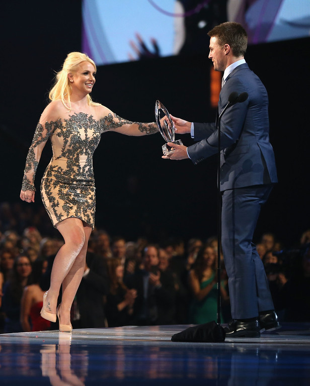Description of . LOS ANGELES, CA - JANUARY 08:  Singer Britney Spears accepts the Favorite Pop Artist award from actor Stephen Amell onstage at The 40th Annual People's Choice Awards at Nokia Theatre L.A. Live on January 8, 2014 in Los Angeles, California.  (Photo by Christopher Polk/Getty Images for The People's Choice Awards)