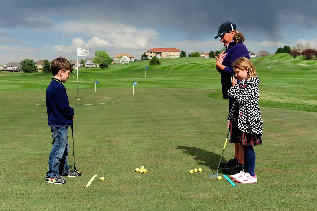 Description of . DENVER, CO - MAY 7: Eva Hellvig, 7, right, touches her nose to help align her golf ball to the center of her body as Cameron Fay, 6, watches during their first class with Nina Krats, center, at Foothills Golf Course on May 7, 2014, in Denver, Colorado. Foothills Park and Recreation is aiming to increase participation in its golf programs, especially in regards to youth involvement. (Photo by Anya Semenoff/The Denver Post)