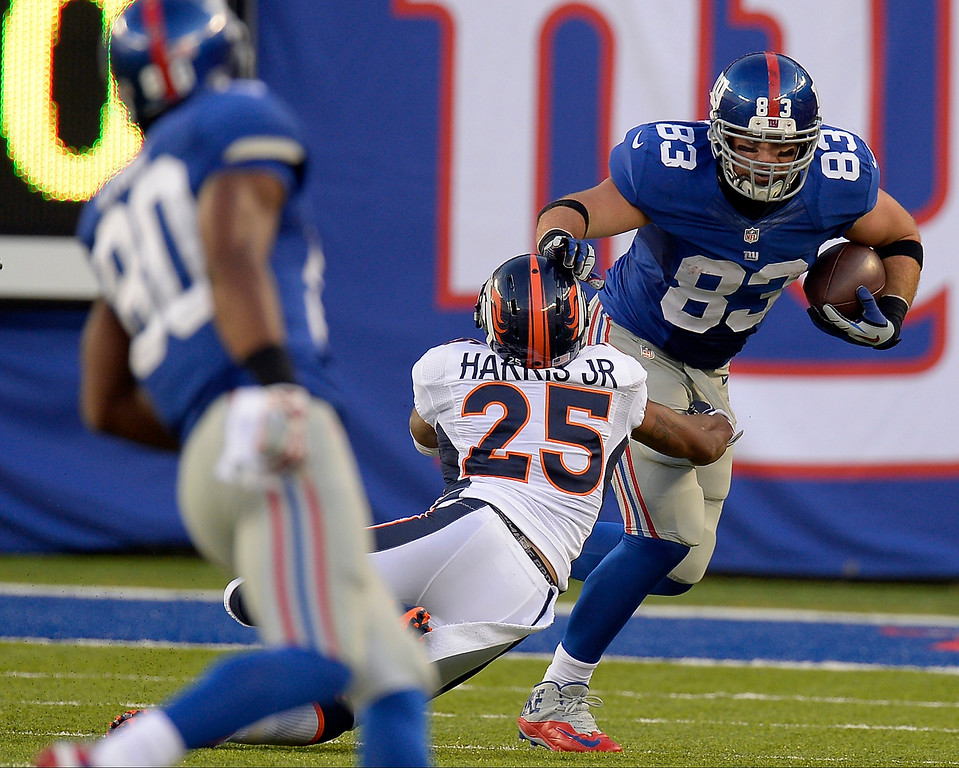 Description of . New York Giants tight end Brandon Myers (83) stiff arms Denver Broncos cornerback Chris Harris (25) as he gains a few yards during the second quarter September 15, 2013 MetLife Stadium. (Photo by John Leyba/The Denver Post)