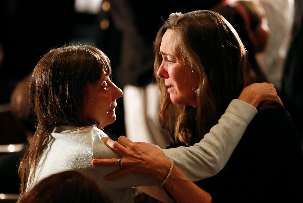 Description of . Women comfort one another during a vigil held at Newtown High School for families of victims of the Sandy Hook Elementary School shooting in Newtown, Connecticut December 16, 2012. U.S. President Barack Obama is visiting Newtown High School to meet with the families of the victims and to thank first responders to the school shooting here, which was one of the deadliest such incidents in the nation's history. REUTERS/Kevin Lamarque