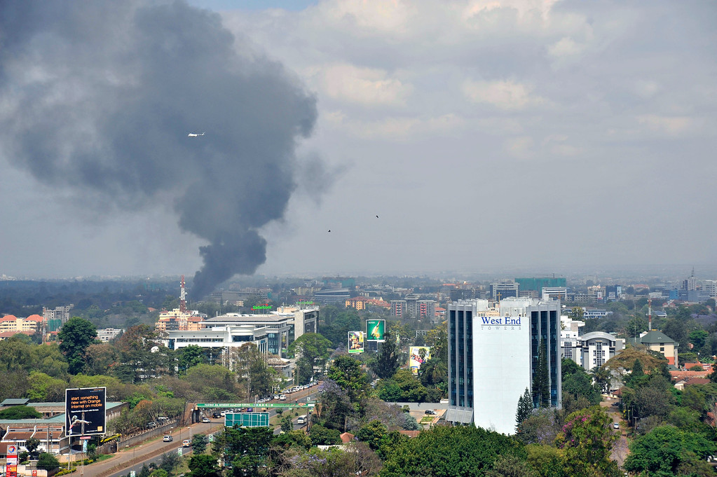Description of . A helicopter and birds fly above as a  plume of black smoke billows rising over the Westgate Mall, following large explosions and heavy gunfire, in Nairobi, Kenya Monday, Sept. 23, 2013. Four large blasts rocked Kenya's Westgate Mall on Monday, sending large plumes of smoke over an upscale suburb as Kenyan military forces sought to rescue an unknown number of hostages held by al-Qaida-linked militants. (AP Photo/Riccardo Gangale)
