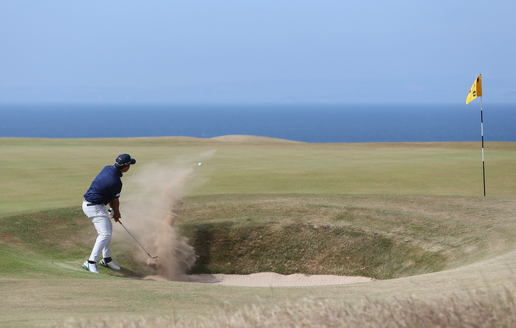 Description of . Shiv Kapur of India plays out of a bunker onto the 11th green during the third round of the British Open Golf Championship at Muirfield, Scotland, Saturday July 20, 2013. (AP Photo/Scott Heppell)