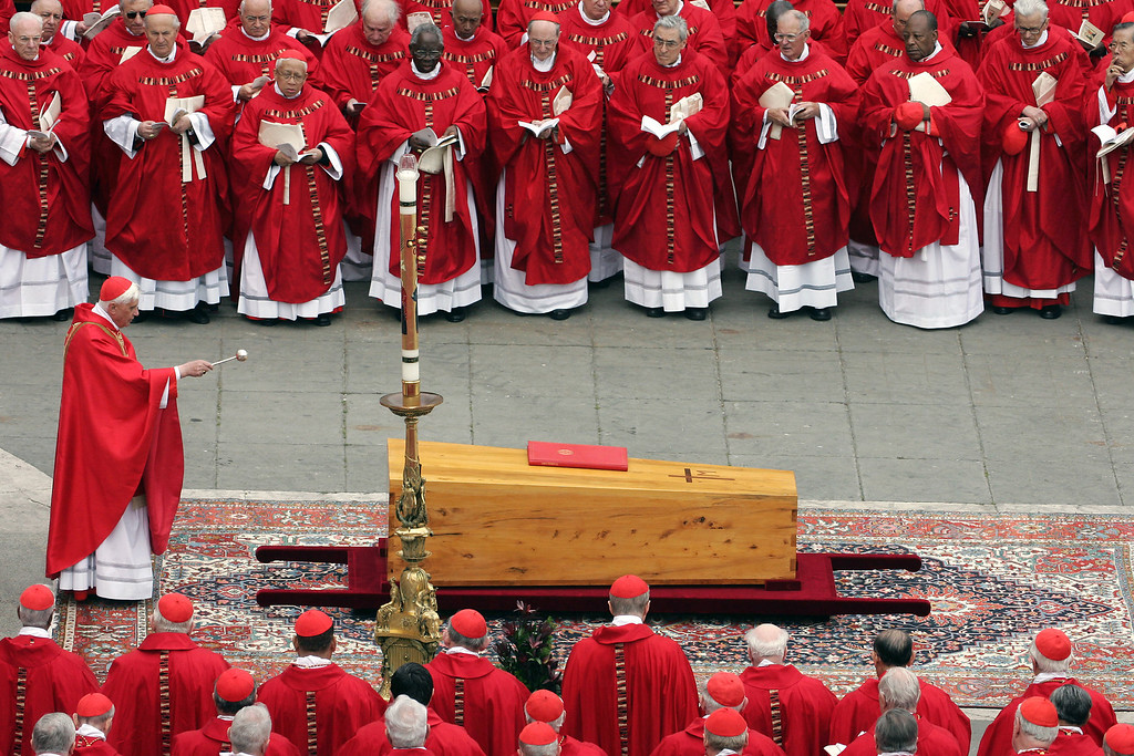 Description of . German Cardinal Joseph Ratzinger blesses the coffin of Pope John Paul II during his funeral mass in St Peter's Square at the Vatican City 08 April 2005. The world looked on Rome as leaders from more than 100 nations and a multitude of mourners gathered for the funeral Friday of Pope John Paul II, one of the most cherished pontiffs in history. PATRICK HERTZOG/AFP/Getty Images