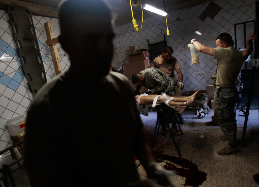 ". An Iraqi Army soldier (L) watches as medics of the Army\'s 2-12 Cavalry Battalion try to save a civilian man injured by a roadside bomb aimed at Iraqi troops by local militants at Joint Security Station Casino in the divided Gazaliyah neighborhood June 29, 2007 in Baghdad, Iraq.  Gazaliyah, one of Baghdad\'s most troubled neighborhoods, is patrolled by the 2-12 Cavalry out of Joint Security Station Casino, one of the field bases that figures prominently in the ""surge\"" strategy of General David Petraeus.  (Photo by Chris Hondros/Getty Images)"