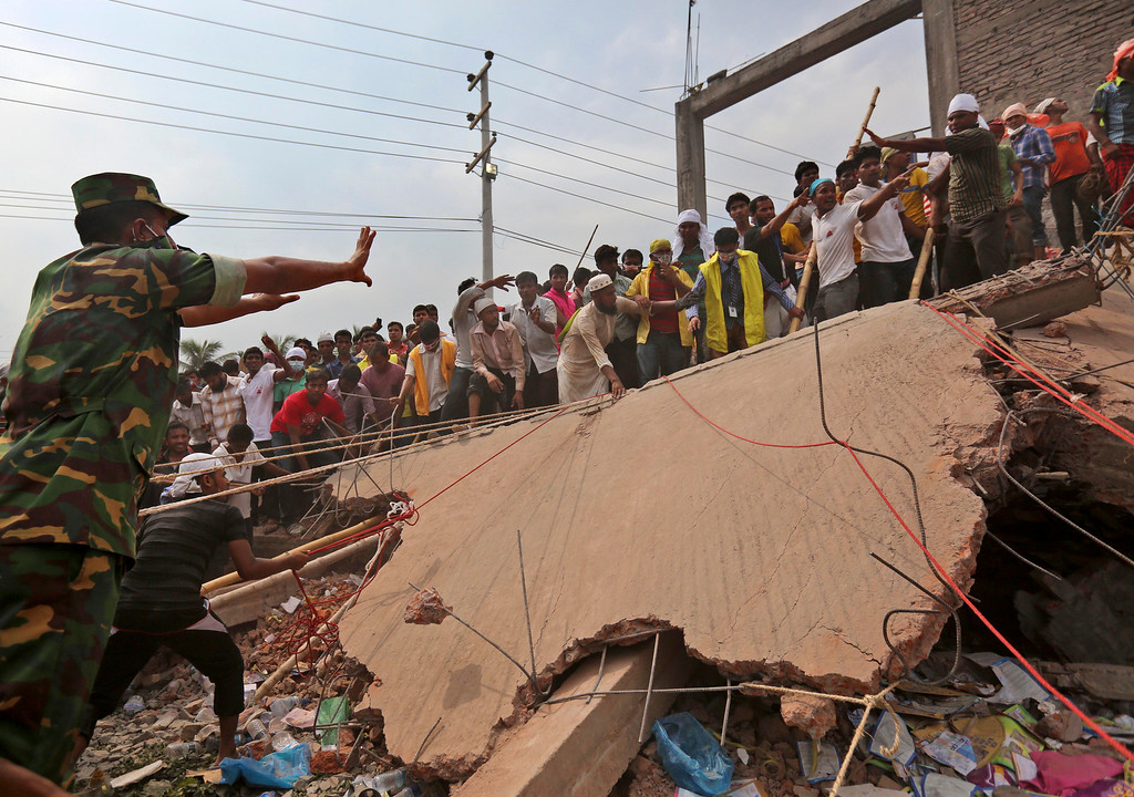 Description of . A Bangladeshi army soldier gestures to civilian volunteer rescuers as they try to lift a large piece of  concrete at the site of a building that collapsed Wednesday in Savar, near Dhaka, Bangladesh, Thursday, April 25, 2013.  (AP Photo/Kevin Frayer)