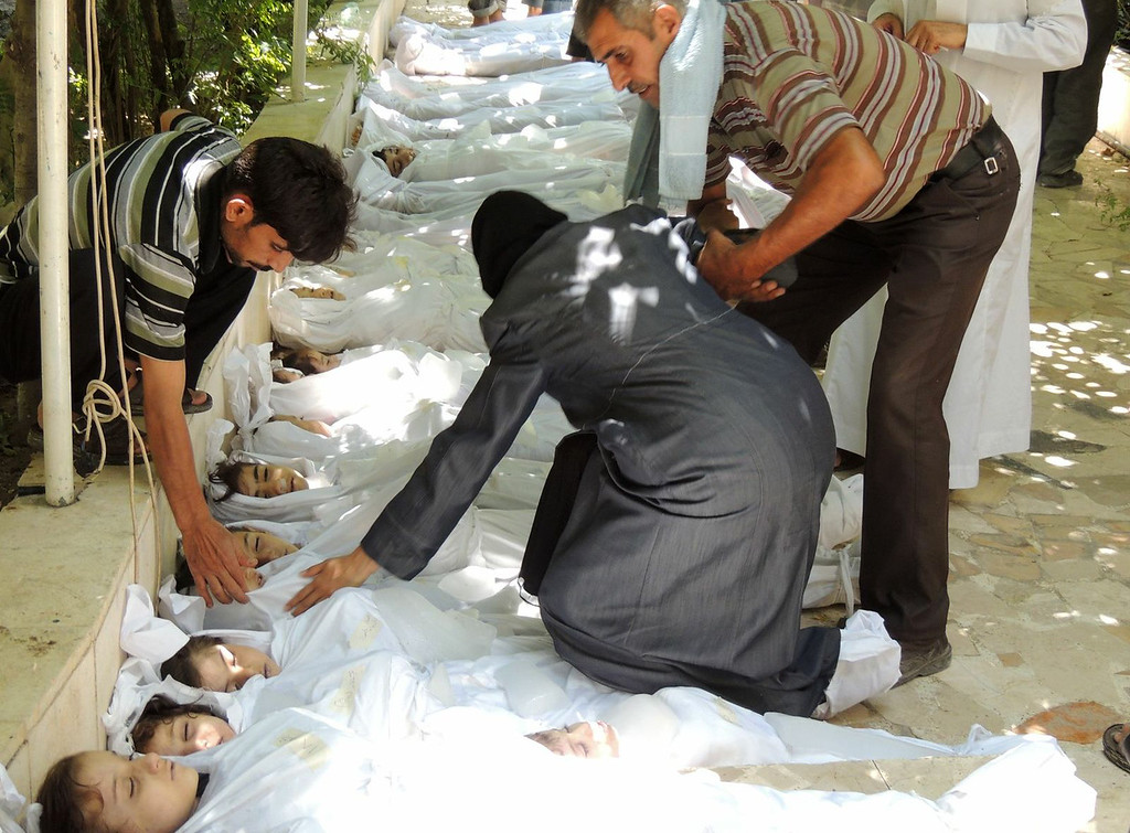 Description of . A handout image released by the Syrian opposition's Shaam News Network shows a woman mourning over a body wrapped in shrouds laid out in a line on the ground with other victims which Syrian rebels claim were killed in a toxic gas attack by pro-government forces in eastern Ghouta, on the outskirts of Damascus on August 21, 2013. The allegation of chemical weapons being used in the heavily-populated areas came on the second day of a mission to Syria by UN inspectors, but the claim, which could not be independently verified, was vehemently denied by the Syrian authorities, who said it was intended to hinder the mission of UN chemical weapons inspectors. DAYA Al-DEEN/AFP/Getty Images