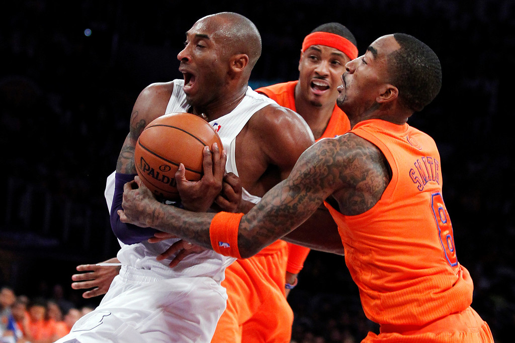Description of . Los Angeles Lakers guard Kobe Bryant, left, is fouled by New York Knicks guard J.R. Smith, right, as forward Carmelo Anthony, center, watches during the first half of their NBA basketball game in Los Angeles, Tuesday, Dec. 25, 2012. (AP Photo/Alex Gallardo)