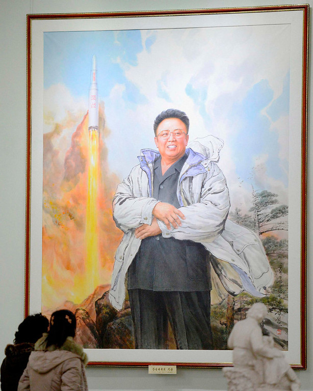 Description of . North Koreans look at a portrait of late leader Kim Jong-il in Pyongyang, on the occasion of his birthday, in this photo taken by Kyodo February 16, 2013. REUTERS/Kyodo