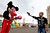 A Syrian refugee boy points a plastic toy pistol at a man in a Mickey Mouse costume on the first day of Eid al-Adha at a park in Beirut October 26, 2012. Muslims around the world celebrate Eid al-Adha, marking the end of the haj, by slaughtering sheep, goats, cows and camels to commemorate Prophet Abraham's willingness to sacrifice his son Ismail on God's command. REUTERS/Jamal Saidi
