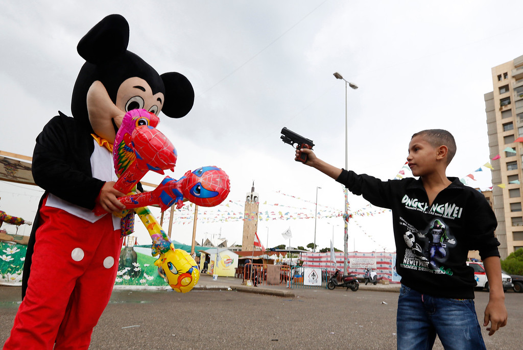 Description of . A Syrian refugee boy points a plastic toy pistol at a man in a Mickey Mouse costume on the first day of Eid al-Adha at a park in Beirut October 26, 2012. Muslims around the world celebrate Eid al-Adha, marking the end of the haj, by slaughtering sheep, goats, cows and camels to commemorate Prophet Abraham's willingness to sacrifice his son Ismail on God's command. REUTERS/Jamal Saidi