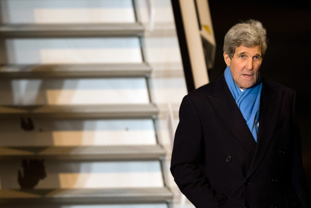 Description of . US Secretary of State John Kerry walks off a plane as he arrives on February 5, 2015 in Munich, southern Germany, where he will attend the Munich Security Conference. The Ukraine conflict, Islamic State group jihadists and the wider