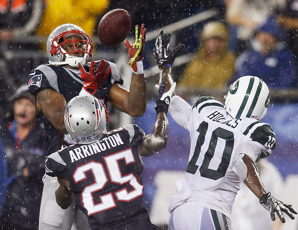 Description of . New England Patriots cornerback Aqib Talib, left, intercepts a pass intended for New York Jets wide receiver Santonio Holmes (10) in front of Patriots cornerback Kyle Arrington (25) during the fourth quarter of an NFL football game Thursday, Sept. 12, 2013, in Foxborough, Mass. (AP Photo/Elise Amendola)