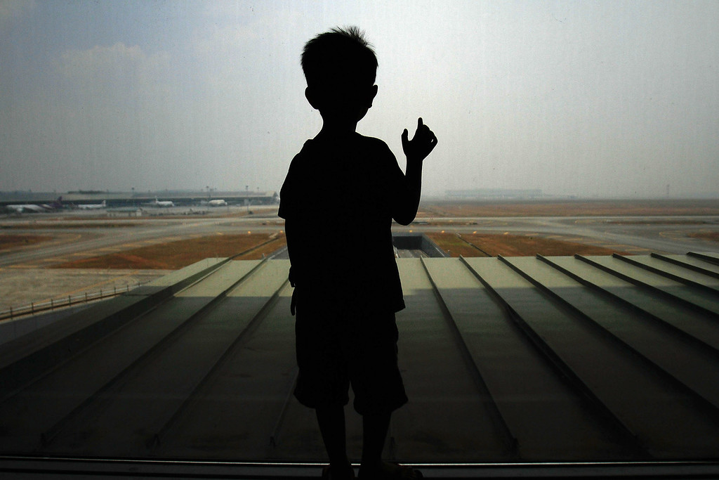 Description of . A boy waits for his family members arrival at Kuala Lumpur International Airport on March 12, 2014 in Kuala Lumpur, Malaysia.  (Photo by Rahman Roslan/Getty Images)