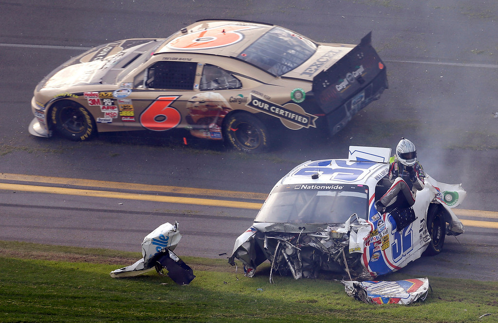 Description of . Driver Kyle Larson climbs out of his car as Trevor Bayne (7) rolls past after a crash at the conclusion of the NASCAR Nationwide Series auto race Saturday, Feb. 23, 2013, at Daytona International Speedway in Daytona Beach, Fla. (AP Photo/Chris O'Meara)