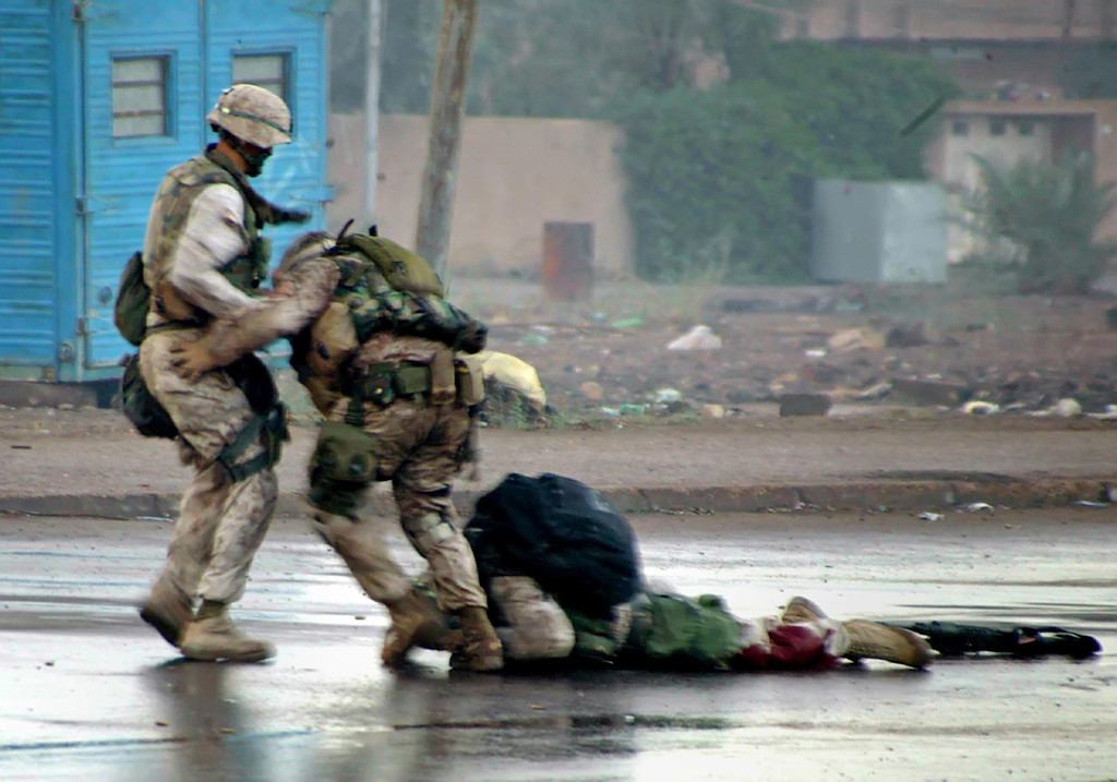 Description of . U.S. Marine platoon Gunnery Sergeant, Ryan P. Shane (C), from the 1st Battalion of the 8th Marine Regiment and another member of 1/8 pull a fatally wounded comrade to safety while under fire during a military operation in the Iraqi western city of Falluja, in this photograph released on December 17, 2004. Seconds later Sgt. Shane was also injured by nearby enemy fire, U.S. Marine officer said. REUTERS/HO/USMC/Cpl. Joel A. Chaverri