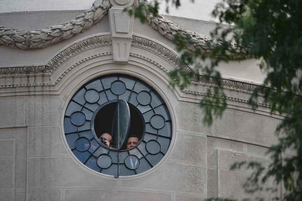 Description of . Men peer through a window of the San Joaquin Episcopal Palace in Rio de Janeiro, Brazil, as they wait for the arrival of Pope Francis, on July 26, 2013. Pope Francis will meet young convicts here and then return to Copacabana beach Friday where 1.5 million Catholics gathered on Rio de Janeiro's seafront to see him speak the previous night in a massive ceremony for World Youth Day festivities. GABRIEL BOUYS/AFP/Getty Images