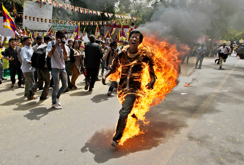 Description of . In this March 26, 2012 file photo, Tibetan exile Jamphel Yeshi screams as he runs engulfed in flames after setting himself on fire at a protest in New Delhi, India, against Chinese President Hu Jintao's visit to India. Yeshi died two days later while hundreds of other activists were being held without charge before the president's arrival. Hu arrived in New Delhi for a summit with India, Russia, Brazil and South Africa. (AP Photo/Manish Swarup, File)