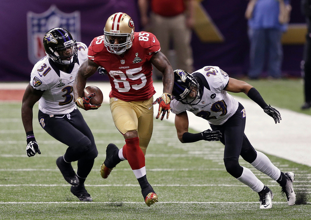 Description of . San Francisco 49ers tight end Vernon Davis (85) runs with the ball as Baltimore Ravens safety Bernard Pollard (31) and cornerback Cary Williams (29) give chase during the first half of the NFL Super Bowl XLVII football game, Sunday, Feb. 3, 2013, in New Orleans. (AP Photo/Bill Haber)