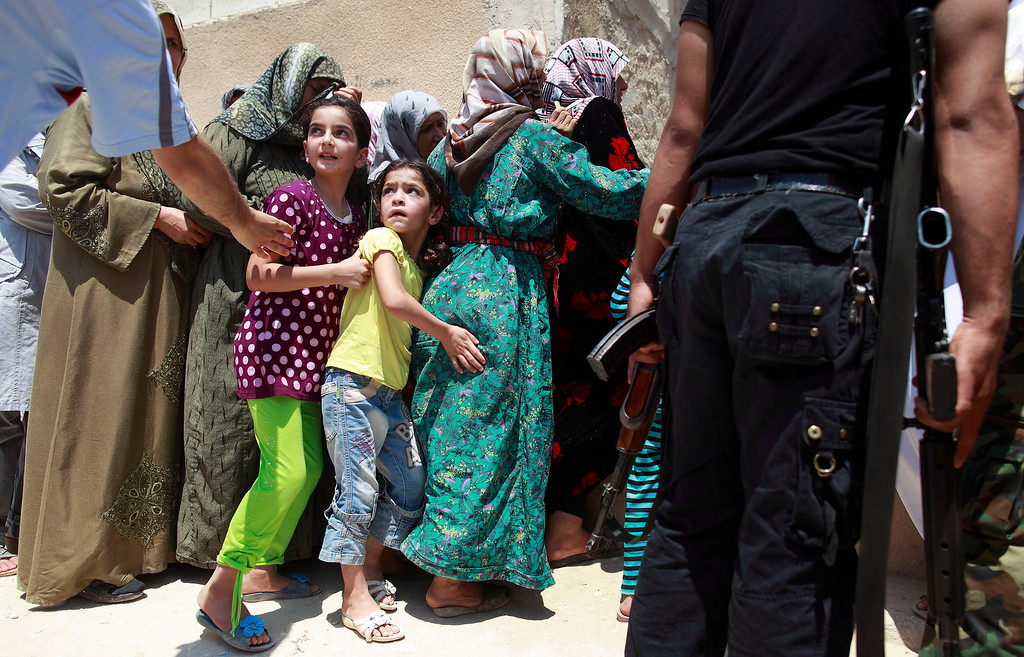 Description of . Girls queue to buy bread at the only bakery serving the outskirts of Idlib province August 1, 2012. REUTERS/Zohra Bensemra