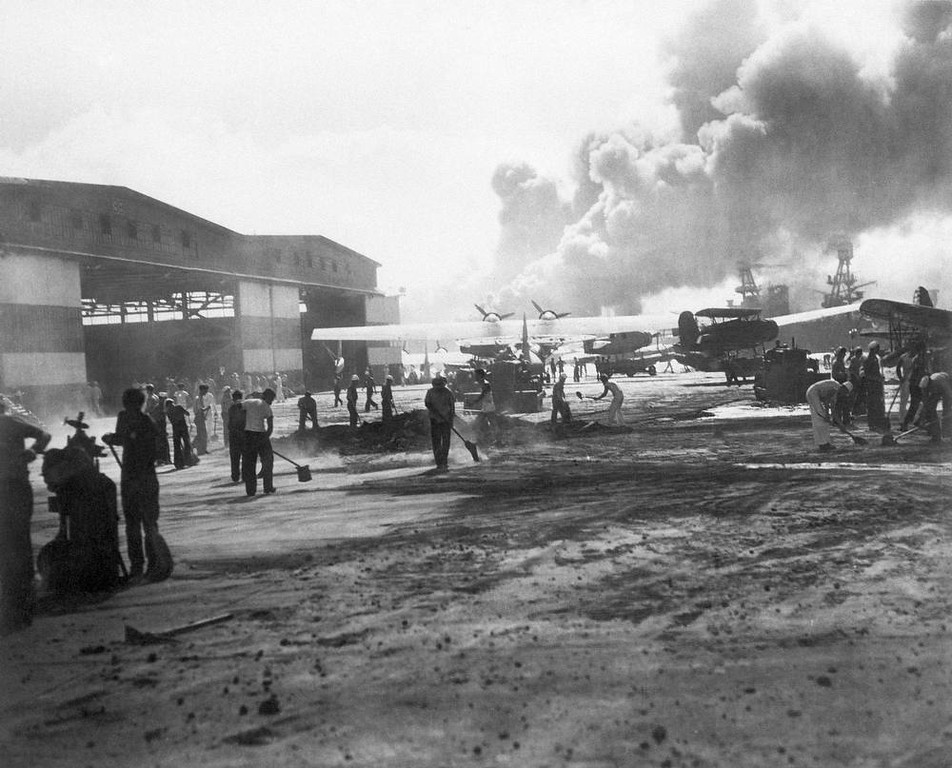 Description of . In this photo provided by the U.S. Navy, hanger No. 6 and the warm-up apron of the air station landing strip on Ford Island in Pearl Harbor, Hawaii shown during the attack, Dec. 7, 1941. (AP Photo/U.S. Navy)