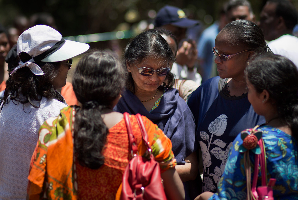 Description of . Relatives and friends of victims console each other at a memorial service marking the one-month anniversary of the Sept. 21 Westgate Mall terrorist attack, in Karura Forest in Nairobi, Kenya Monday, Oct. 21, 2013. (AP Photo/Ben Curtis)