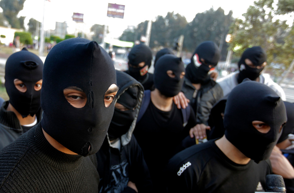 . Egyptian masked protesters, who call themselves the black eagles and describes themselves as peaceful but are prepared to defend any attacks against protesters, gather near the presidential palace in Cairo, Egypt, Friday, Jan. 25, 2013. Two years after Egypt\'s revolution began, the country\'s schism was on display Friday as the mainly liberal and secular opposition held rallies saying the goals of the pro-democracy uprising have not been met and denouncing Islamist President Mohammed Morsi. (AP Photo/Amr Nabil)