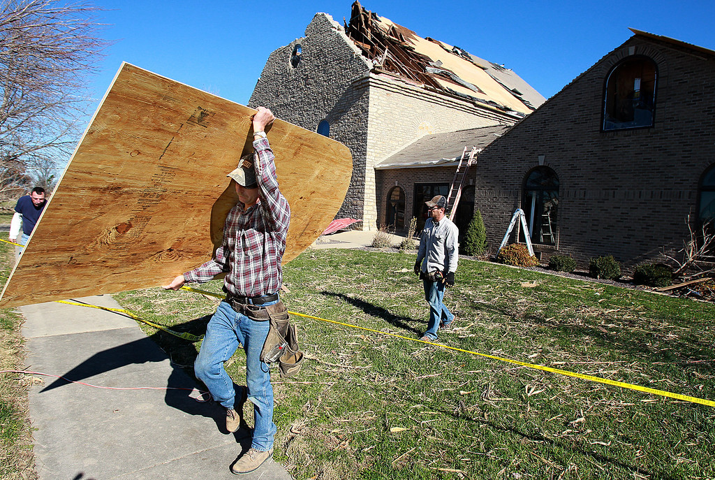 Description of . Matt Brandmeyer of Bartelso carries plywood used to repair the damaged St. John's Lutheran Church Monday, Nov. 18, 2013,  in New Minden, Ill. (AP Photo/ Belleville News-Democrat,Steve Nagy)