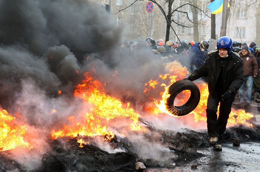 Description of . An anti-government protester throws a tire in a barricade on the streets of downtown Kiev, Ukraine, 18 February 2014. A least three protesters were killed in clashes with police on 18 February, Ukrainian opposition activists say. EPA/IGOR KOVALENKO