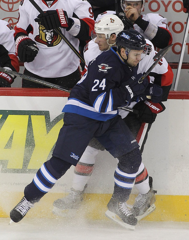 Description of . WINNIPEG, MB - JANUARY 19:  Grant Clitsome #24 of the Winnipeg Jets takes Jim O\'Brien #18 of the Ottawa Senators to the boards during period action on January 19, 2013 at the MTS Centre in Winnipeg, Manitoba, Canada. (Photo by Marianne Helm/Getty Images)