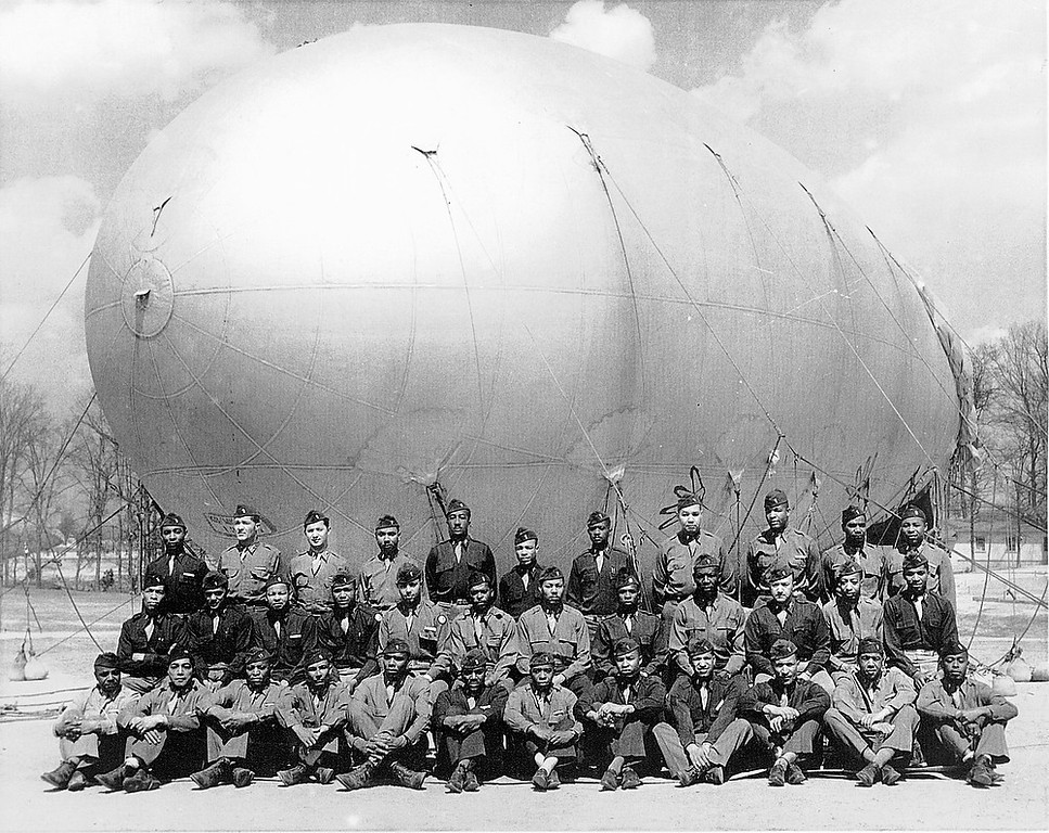 Description of . Art Brooks and other members of the 320th battalion gather for a photograph June 5, 1944, the morning before D-Day with an anti-aircraft barrage balloon. (Art Brooks obit photo)