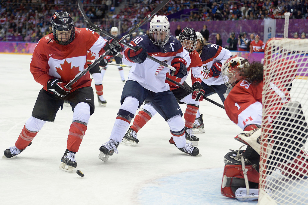 Description of . SOCHI, RUSSIA - FEBRUARY 20: Meghan Duggan (10) of the U.S.A. looks for a shot near the goal as Jocelyne Larocque (3) of the Canada and Shannon Szabados (1) of the Canada defend during the first period of the women's gold medal ice hockey game. Sochi 2014 Winter Olympics on Thursday, February 20, 2014 at Bolshoy Ice Arena. (Photo by AAron Ontiveroz/ The Denver Post)
