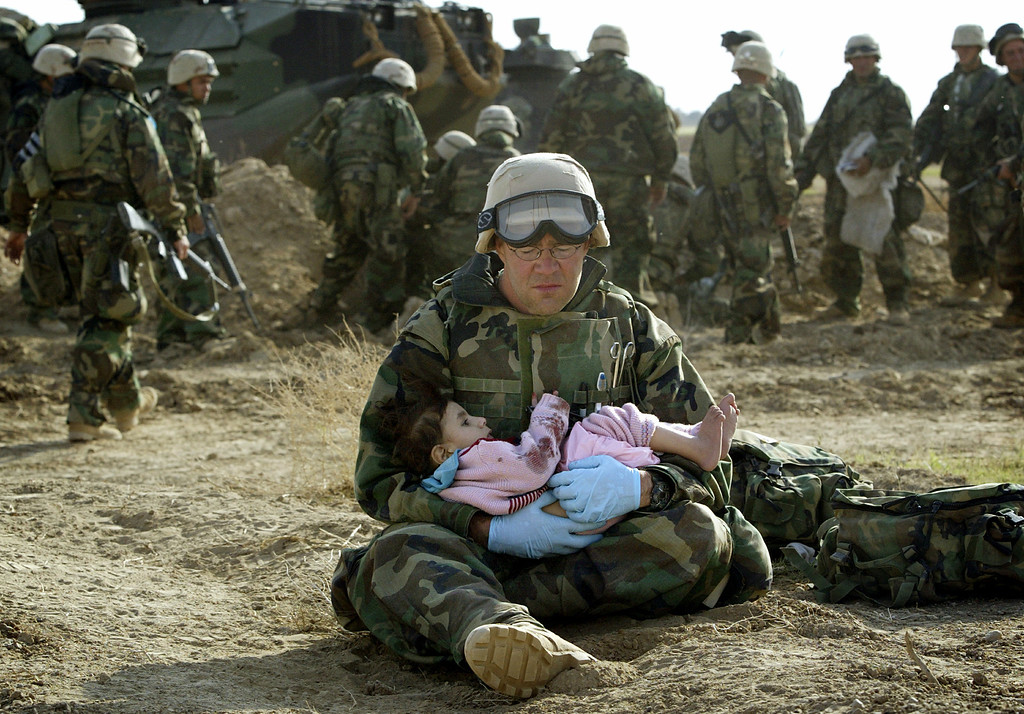 Description of . U.S. Navy Hospital Corpsman HM1 Richard Barnett, assigned to the 1st Marine Division, holds an Iraqi child in central Iraq on March 29, 2003. Confused front line crossfire ripped apart an Iraqi family after local soldiers appeared to force civilians towards positions held by U.S. Marines. REUTERS/Damir Sagolj
