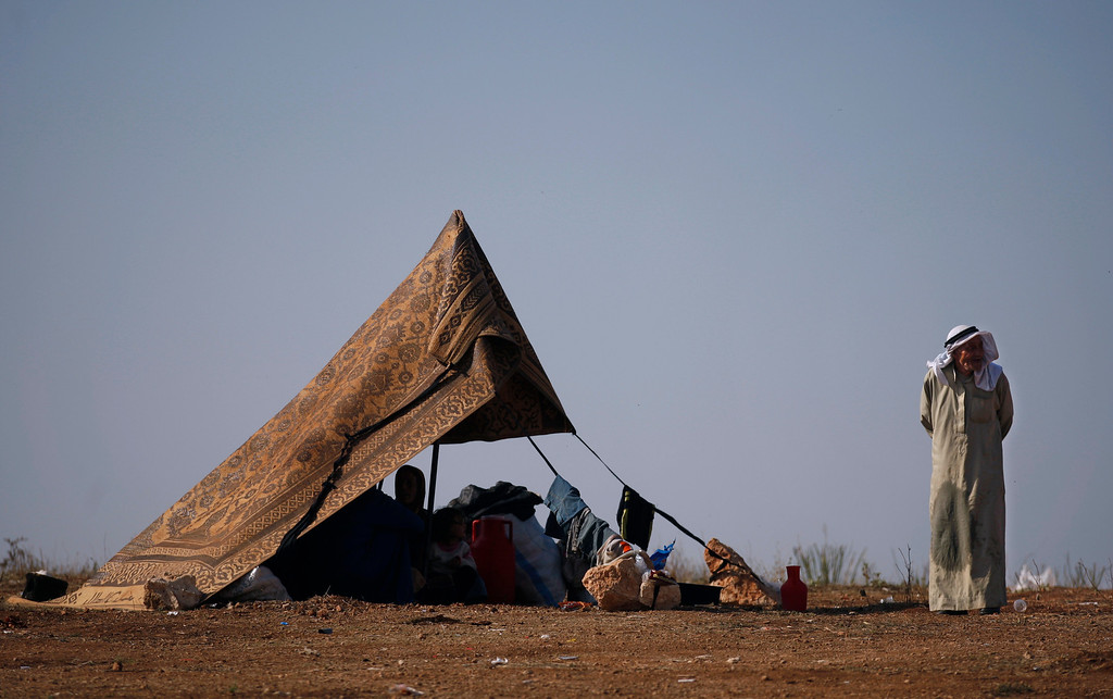 Description of . FILE - A Syrian family who fled from the violence in their village, sit in a tent at a displaced camp, in the Syrian village of Atma, near the Turkish border with Syria, Monday, Nov. 5, 2012. (AP Photo/ Khalil Hamra, File)