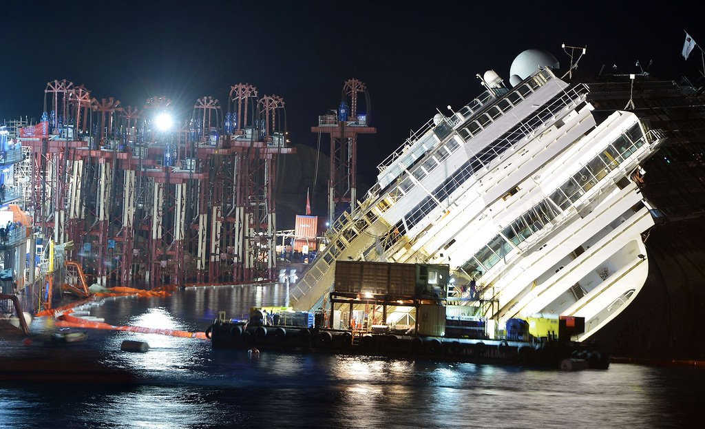 Description of . The wreck of Italy's Costa Concordia cruise ship begins to emerge from water on September 16, 2013 near the harbor of Giglio Porto. Salvage workers attempt to raise the cruise ship in the largest and most expensive maritime salvage operation in history, so-called