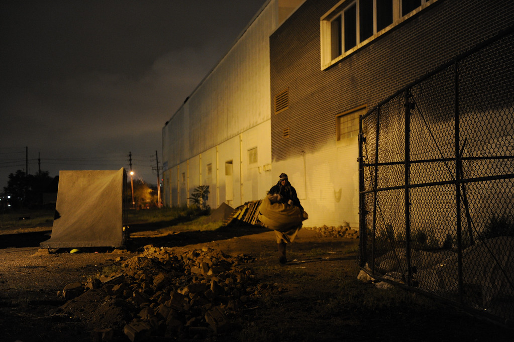 Description of . As darkness sets in, Angel, a heroin addict living on the streets of Denver, moves her sleeping bag to set it up next to a dumpster. On cold nights, Angel has a hard time finding a vein to shoot up.