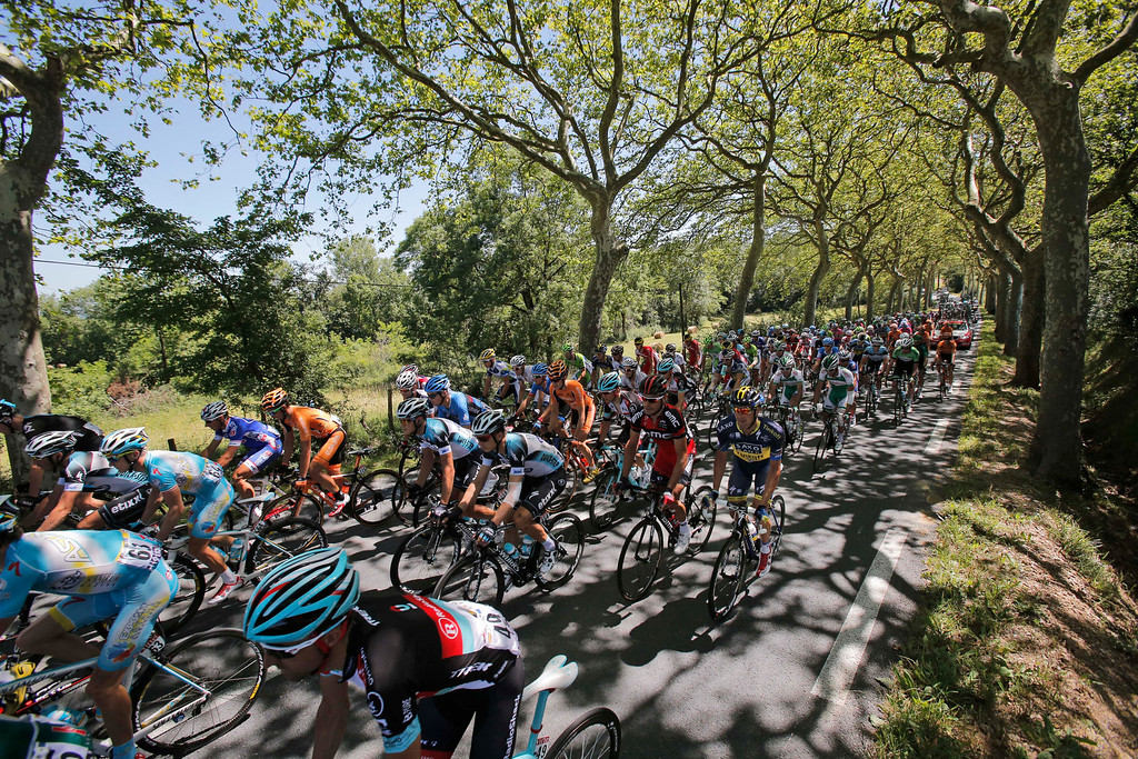. The pack with Spain\'s Alberto Contador, right in dark blue and yellow jersey rides on a tree-lined road during stage eight of the Tour de France cycling race over 195 kilometers (122 miles) with start in Castres and finish in Ax 3 Domaines, Pyrenees region, France, Saturday July 6 2013. (AP Photo/Christophe Ena)