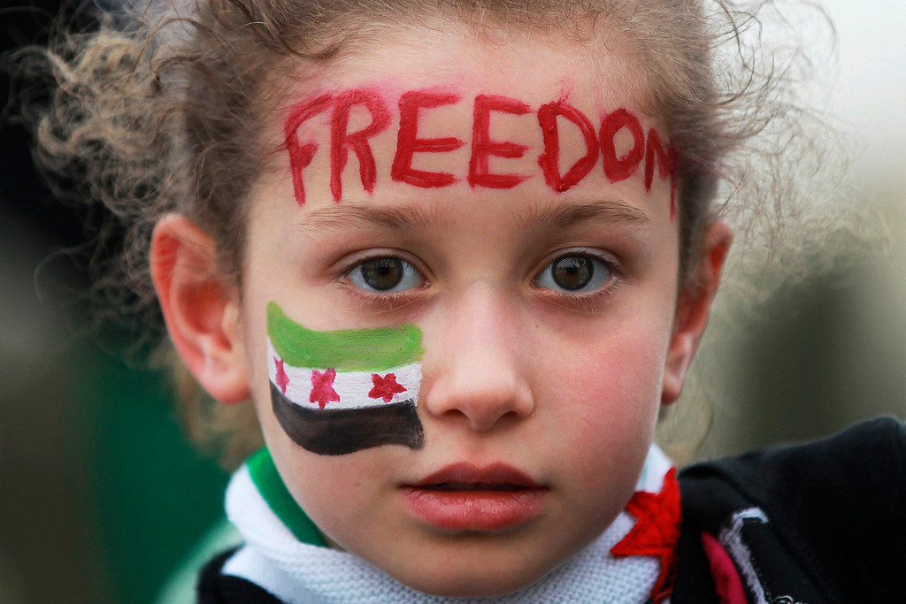 Description of . A Syrian girl living in Jordan, with her face painted with the Syrian revolutionary flag, attends a protest marking two years since the start of the uprising, in front of the Syrian embassy in Amman March 15, 2013. REUTERS/Muhammad Hamed