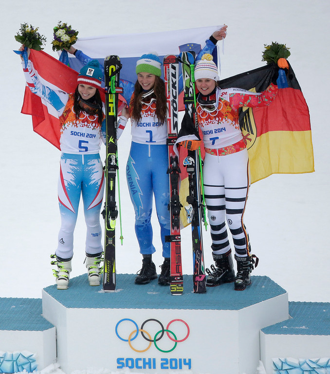 Description of . Women's giant slalom winners, from left, Austria's Anna Fenninger (silver), Slovenia's Tina Maze (gold) and Germany's Viktoria Rebensburg (bronze), pose for photographers on the podium at the Sochi 2014 Winter Olympics, Tuesday, Feb. 18, 2014, in Krasnaya Polyana, Russia. (AP Photo/Charlie Riedel)