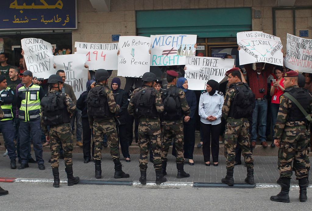 Description of . Protesters hold banners as U.S. President Barack Obama's motorcade travels through the West Bank town of Bethlehem on his way to the Church of the Nativity, March 22, 2013.   REUTERS/Jason Reed