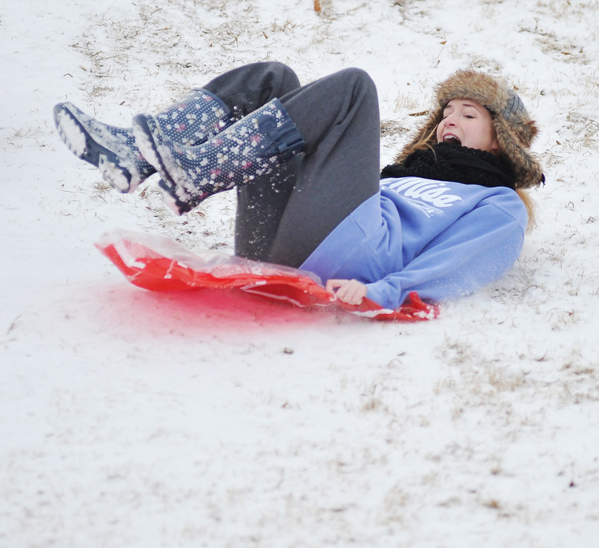 Description of . University of Mississippi student Kathryn Davis slides down a hill, in Oxford, Miss. on Tuesday, Feb. 10, 2014.  There is another chance of snow or sleet in northern Mississippi for Tuesday night, with low temperatures in the low to mid-twenties.  (AP Photo/Oxford Eagle, Bruce Newman)