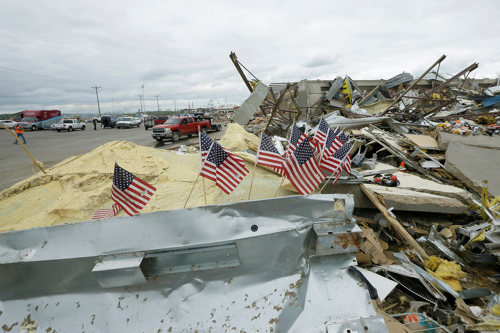Description of . Small flags fly at the destroyed Vilonia Shopping enter in Vilonia, Ark., Wednesday, April 30, 2014. A tornado struck the town late Sunday.  Along stretches of damaged houses, volunteers with chain saws cleared trees from across homes, driveways and streets.  (AP Photo/Danny Johnston)