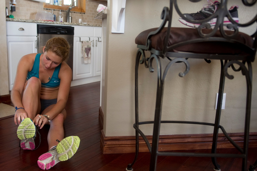 Description of . Olympic downhill skier Mikaela Shiffrin puts on her shoes in her kitchen before running four miles uphill as part of her training regime for this year's Winter Olympics, in Beaver Creek Co. on July 15, 2013. (Photo By Grant Hindsley/The Denver Post)