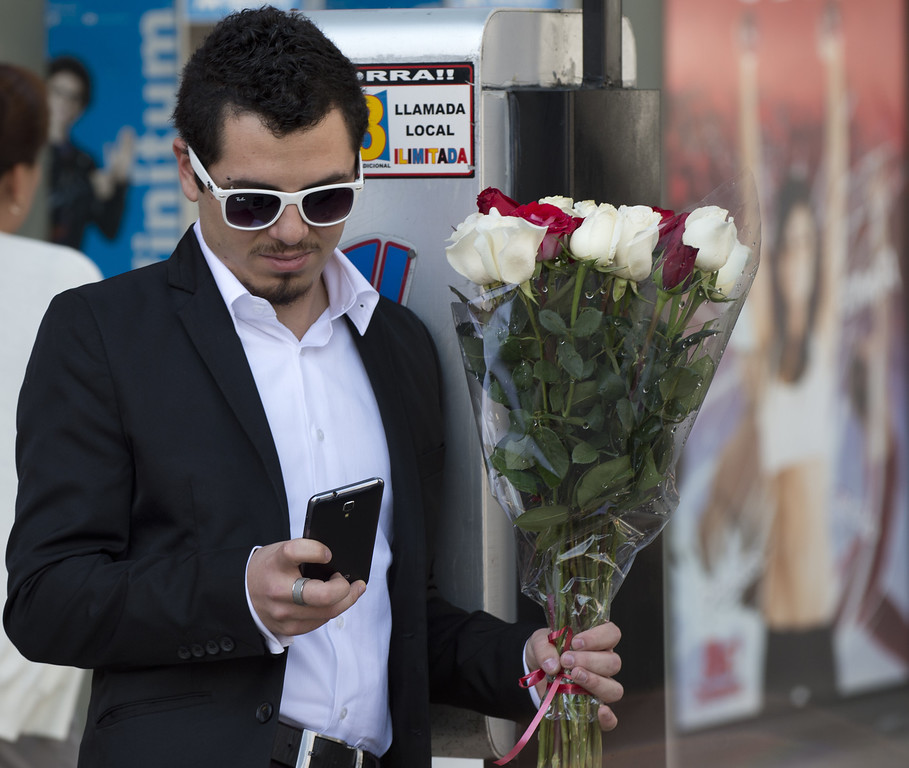 Description of . A man checks his mobile phone as he holds a bunch of flowers at the Republic Square in Mexico City on St Valentine's Day, on February 14, 2013.  AFP PHOTO/Yuri  CORTEZ/AFP/Getty Images