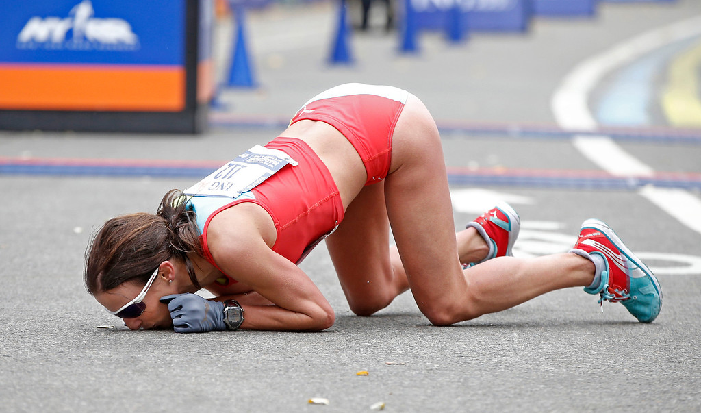 Description of . Sabrina Mockenhaupt of Germany kisses the ground after finishing seventh in the women's division of the New York City marathon, Sunday, Nov. 3, 2013, in New York. (AP Photo/Kathy Willens)
