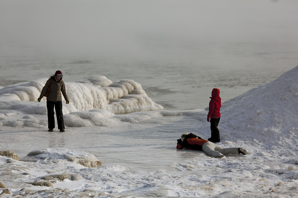 . A family braves the cold to take photographs along the icy shore of Lake Michigan as temperatures remain in the negative digits on January 7, 2014 in Milwaukee, Wisconsin. A \'polar vortex\' of frigid air centered on the North Pole dropped temperatures to the negative double digits at its worst. (Photo by Darren Hauck/Getty Images)