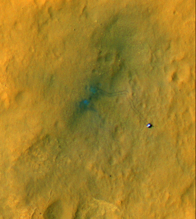 Description of . FILE - This image provided by NASA/JPL-Caltech/Univ. of Arizona, shows tracks from the first drives of NASA's Curiosity rover, captured by the High-Resolution Imaging Science Experiment (HiRISE) camera on NASA's Mars Reconnaissance Orbiter. The image's color has been enhanced to show the surface details better. The two marks seen near the site where the rover landed formed when reddish surface dust was blown away by the rover's descent stage, revealing darker basaltic sands underneath. Similarly, the tracks appear darker where the rover's wheels disturbed the top layer of dust. Observing the tracks over time will provide information on how the surface changes as dust is deposited and eroded. (AP Photo/NASA/JPL-Caltech/Univ. of Arizona)